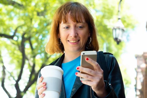 Femme rousse jeune tape le message avec le téléphone mobile. Photo Premium