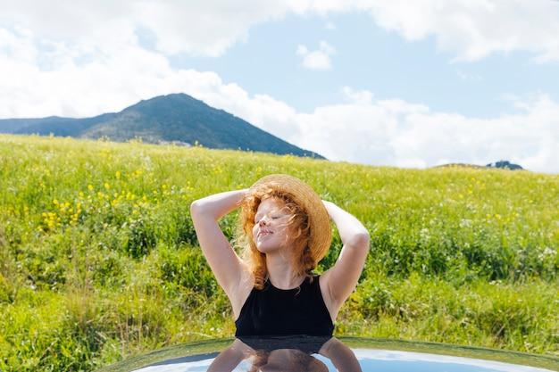 Femme rousse profitant du soleil Photo gratuit