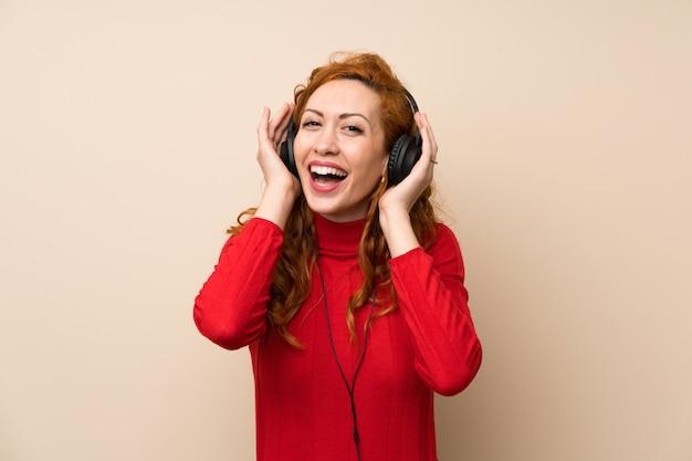 Femme rousse avec pull à col roulé, écouter de la musique avec des écouteurs Photo Premium