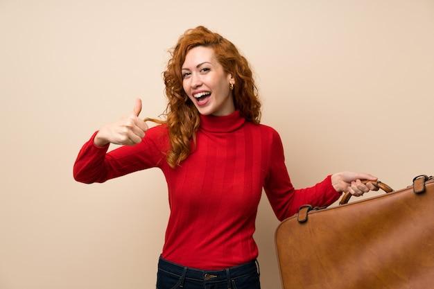 Femme rousse avec un pull à col roulé tenant une mallette vintage Photo Premium