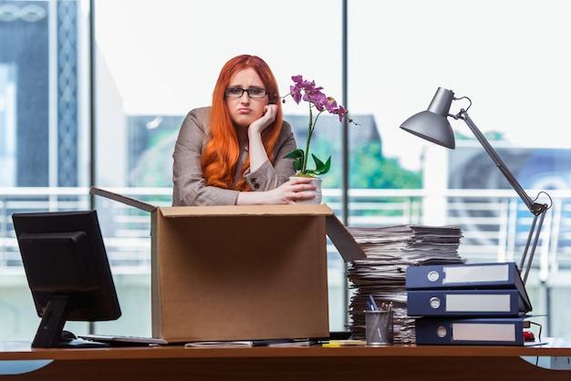 Femme rousse qui déménage dans son nouveau bureau et qui range ses affaires Photo Premium