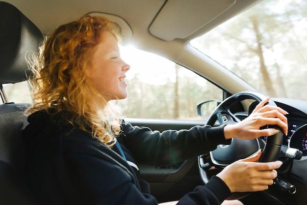 Femme rousse souriante au volant d'une voiture Photo gratuit