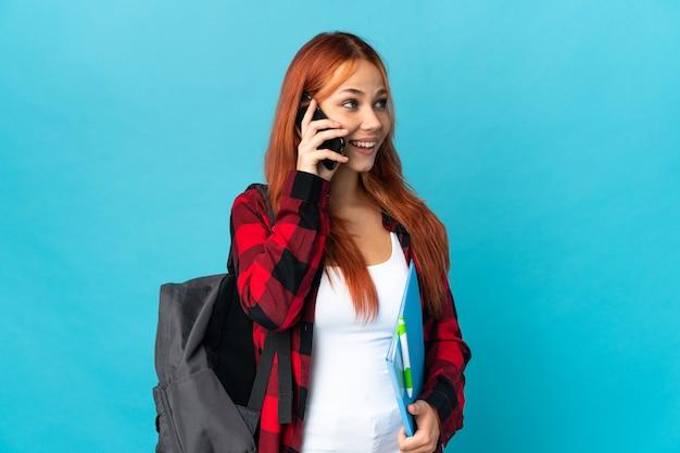 Femme Russe étudiante Isolée Sur Bleu En Gardant Une Conversation Avec Le Téléphone Mobile Photo Premium