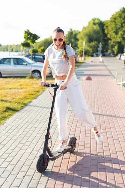 Femme s'amusant sur un scooter Photo gratuit