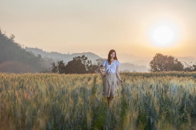 Femme s'amuser au champ d'orge au moment du coucher du soleil Photo Premium