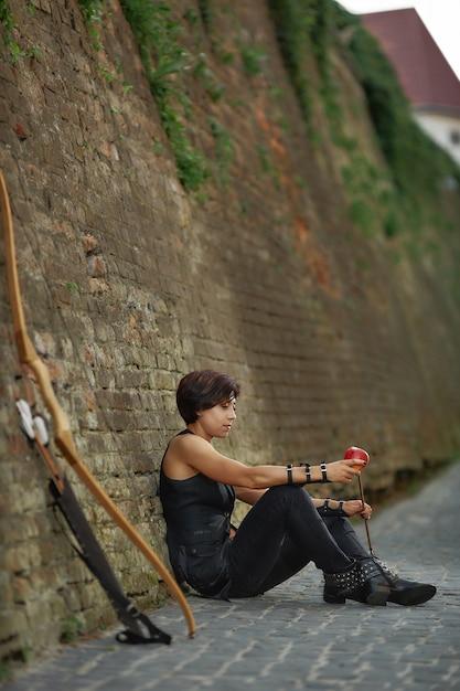 Femme S'appuyant Sur Le Mur De Briques Près De L'arc Et Des Flèches. Photo Premium