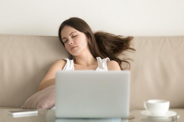Femme s'endormir sur le canapé devant un ordinateur portable Photo gratuit