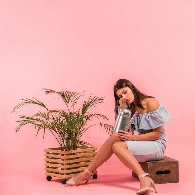 Femme s'ennuie assis avec arrosoir près de la plante Photo gratuit