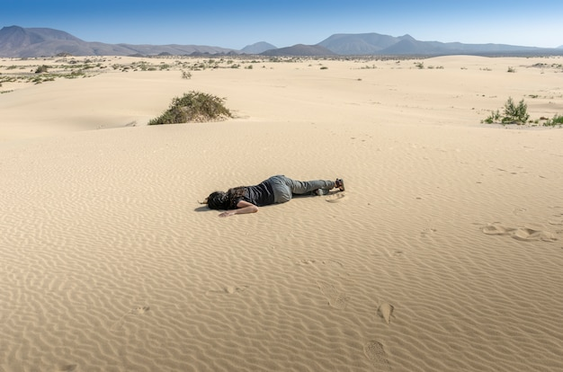 Femme s'est évanouie au milieu du sable du désert. elle est déshydratée et perdue. île de fuerteventura. Photo Premium