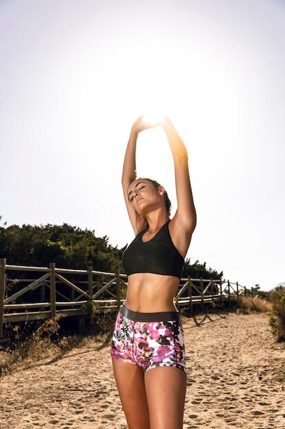 Femme s'étendant avant de courir sur le sable Photo gratuit