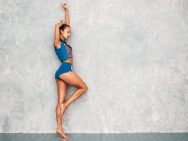 Femme S'étendant Avant La Formation Près Du Mur Gris En Studio Photo gratuit