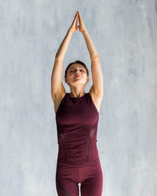 Femme s'étendant pendant sa formation de yoga Photo gratuit