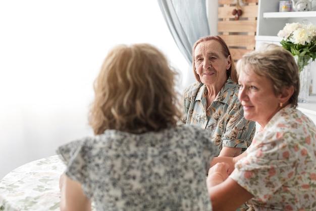 Femme avec sa mère et sa grand-mère assis ensemble dans la cuisine Photo gratuit