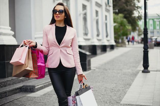 Femme avec un sac dans une ville Photo gratuit