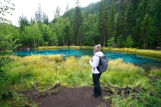 Femme avec sac à dos, randonnée, forêt et lac, concept aventure Photo Premium