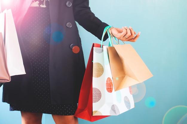 Femme avec des sacs à provisions sur les mains, concept commercial, vendredi noir, jour de thanksgiving Photo Premium