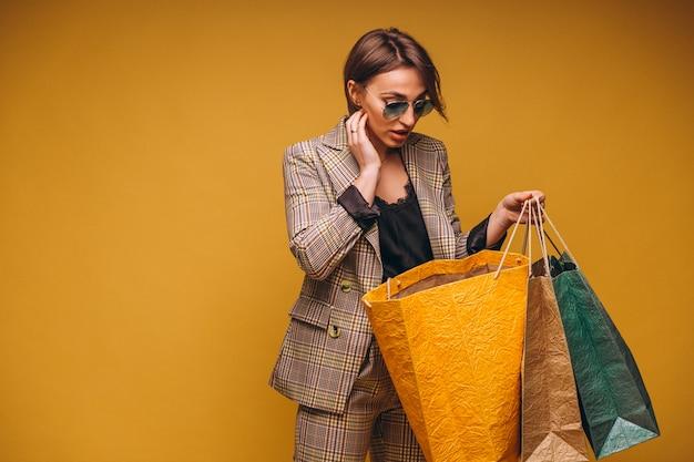Femme avec des sacs à provisions en studio sur fond jaune isolé Photo gratuit