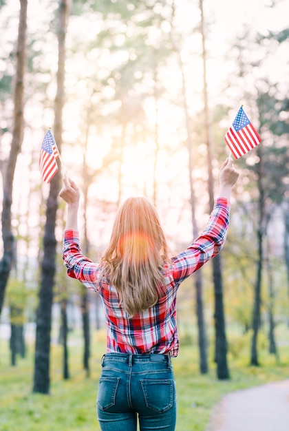 Femme sans visage avec des drapeaux des états-unis au soleil Photo gratuit
