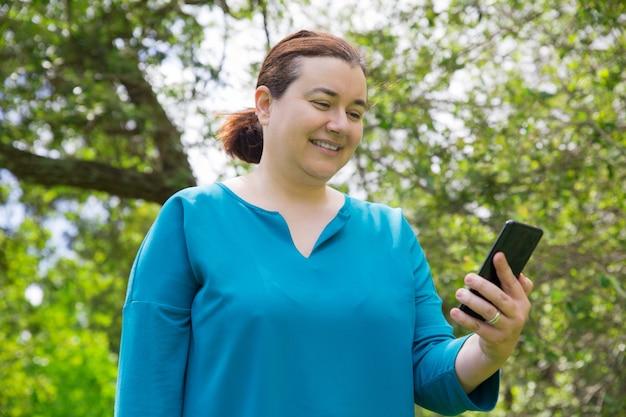 Femme satisfaite positive avec téléphone portable Photo gratuit