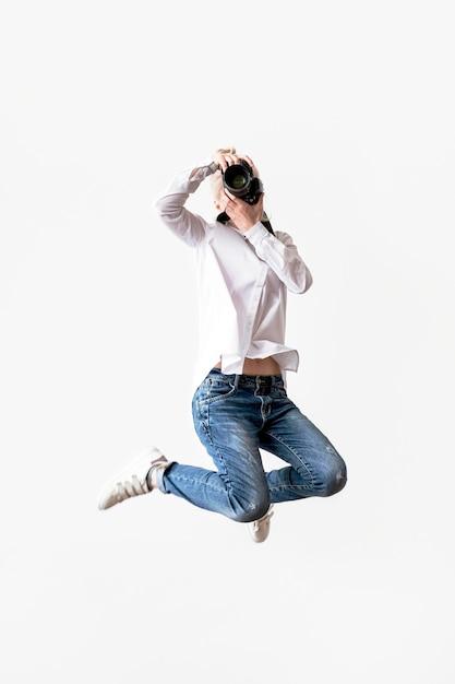 Femme Sautant Et Utilisant Son Appareil Photo Photo gratuit