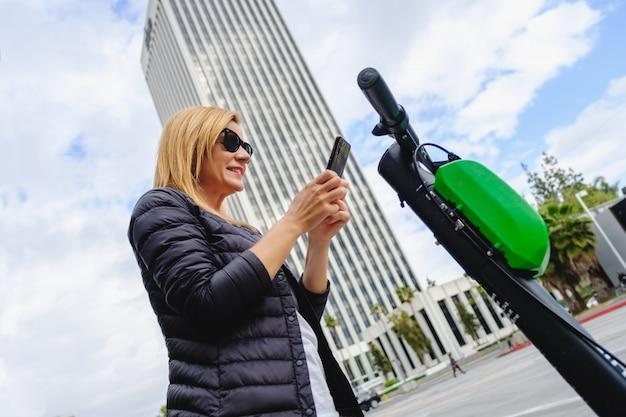Femme Scannant Le Code Qr Avec Son Téléphone Pour Louer Un Scooter électrique Photo Premium