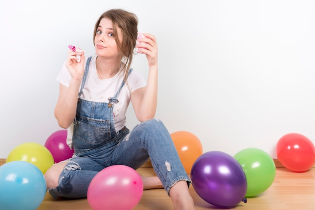 Femme sceptique avec coupe et corne de fête Photo gratuit