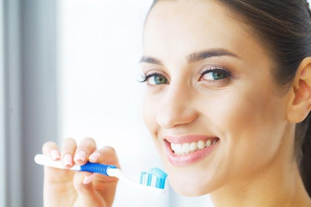 Femme Se Brosser Les Dents Blanches Saines Avec Une Brosse. Photo Premium