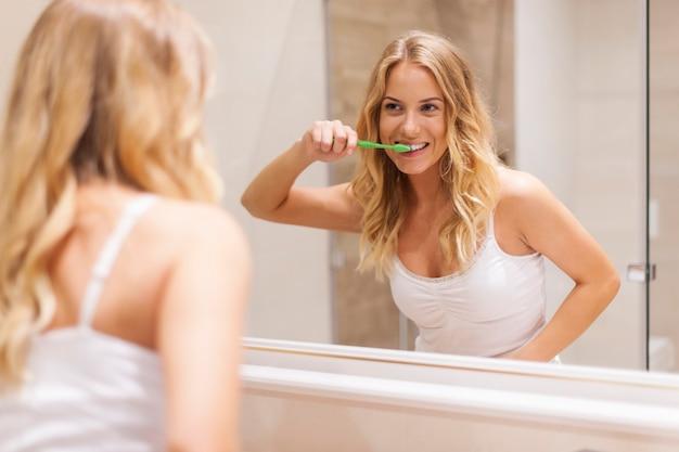 Femme Se Brosser Les Dents Devant Le Miroir Photo gratuit