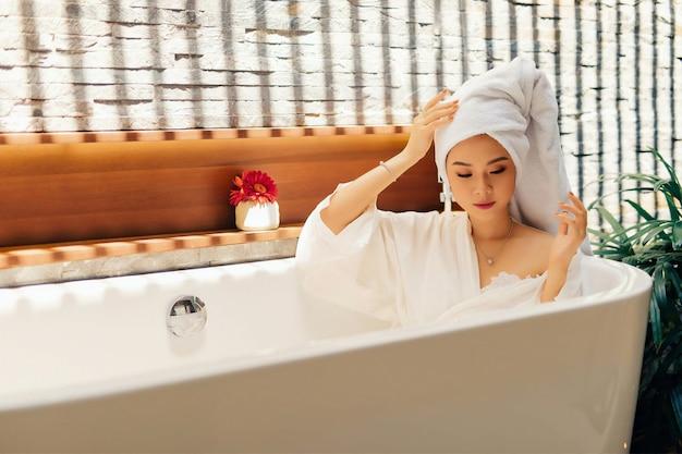 Femme se détendre dans la baignoire sous le soleil Photo Premium