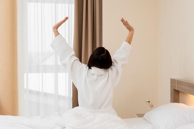 Femme se détendre dans une chambre d'hôtel Photo gratuit