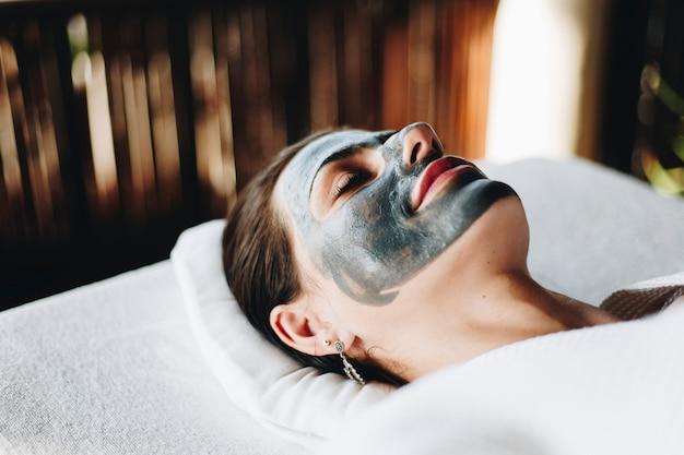 Femme se détendre avec un masque facial au spa Photo Premium