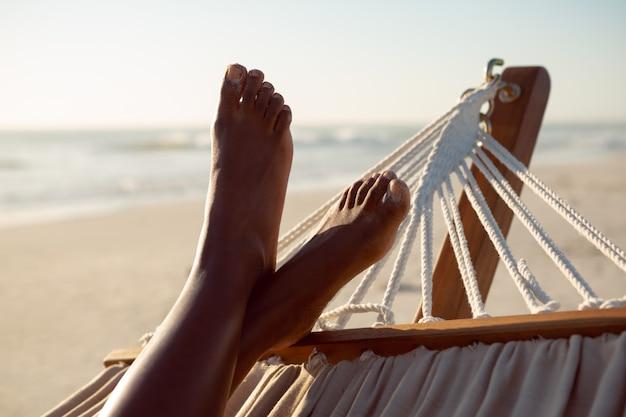 Femme se détendre avec les pieds dans un hamac sur la plage Photo gratuit