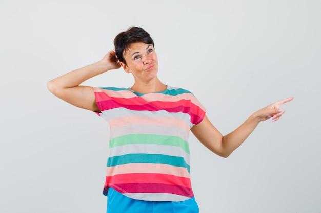 Femme Se Gratter La Tête, Pointant Vers Le Côté En T-shirt Rayé Et à L'hésitation Photo gratuit