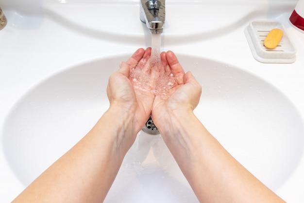 Une femme se lave les mains avec de l'eau dans un lavabo Photo Premium