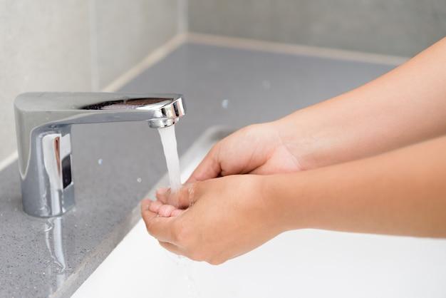 Femme se laver les mains avec du savon sous le robinet avec de l'eau dans la salle de bain. Photo Premium