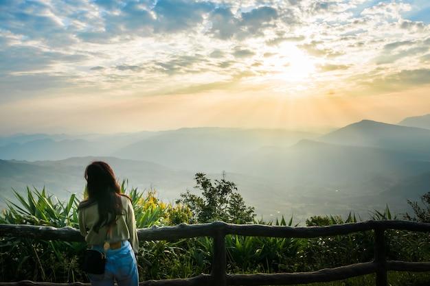 Une Femme Se Lève Pour Regarder La Vue Et Le Soleil Se Lever Dans Le Ciel Du Matin. Photo Premium