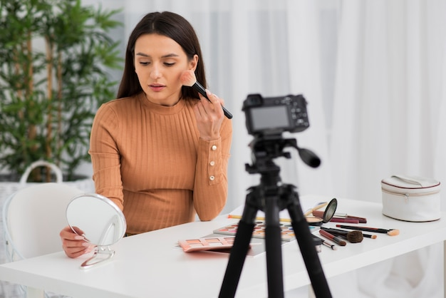 Femme se maquillant à la caméra Photo gratuit