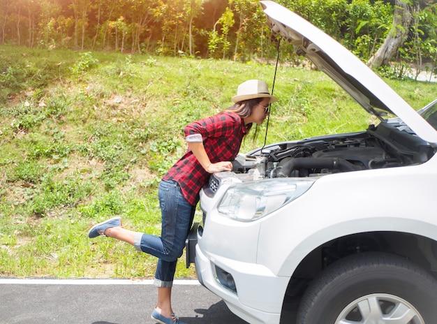 Femme se penchant pour vérifier le moteur de sa voiture après une panne Photo Premium