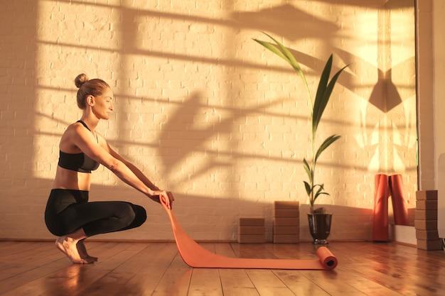 Femme se préparant pour faire du yoga, allongée sur une natte sur le sol Photo Premium