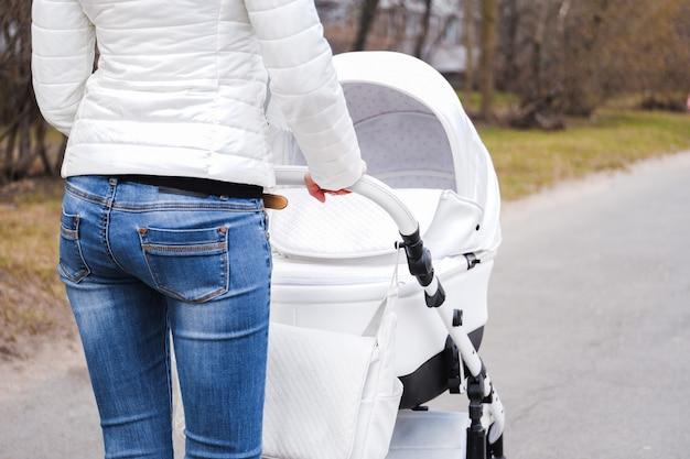 Femme se promenant avec un landau vue arrière Photo Premium