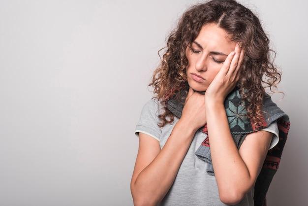 Femme se sentir somnolent avoir froid et toux sur fond gris Photo gratuit