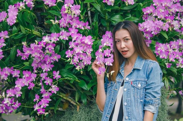 Une femme se tenant debout sur une belle orchidée rose en fleurs Photo Premium