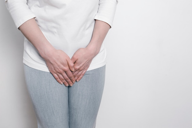 Une femme se tient les mains pour un entrejambe douloureux. problèmes gynécologiques dans le bas-ventre. inflammation de la vessie. Photo Premium