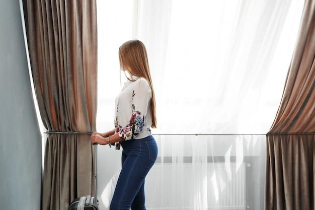 Femme Se Tient Près De La Fenêtre Dans La Chambre D'hôtel Au Moment Du Matin Photo Premium