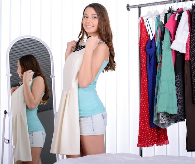Femme se tient près de son portant avec beaucoup de robes Photo Premium