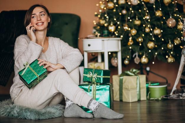 Femme, séance, arbre noël, achats, téléphone Photo gratuit