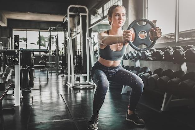 Femme, séance entraînement, poids, plaque, gymnase Photo Premium