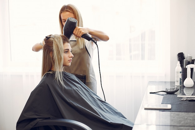 Femme séchant les cheveux dans un hairsalon Photo gratuit