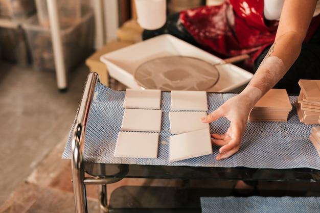 Femme séchant les petites tuiles blanches en atelier Photo gratuit