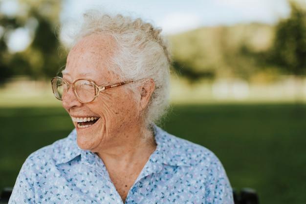 Femme senior gaie assise dans le parc Photo Premium